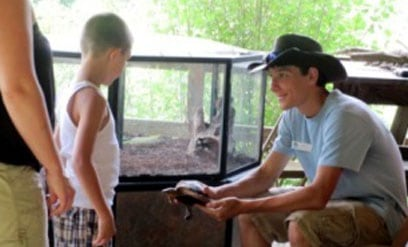 Young Naturalist shows a turtle to a child