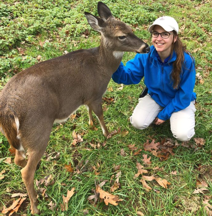 A Nature Center employee with a white tailed deer.