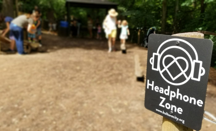A KultureCity Headphone Zone sign at a Nature Play area.